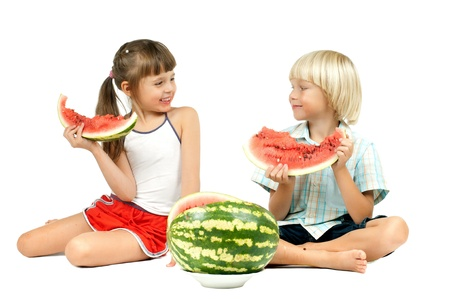 two children  eating watermelon and smile, on white background, isolated photo