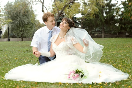 cutie:  cutie happy married  couple  on nature in park ,  sit on lawn and smile Stock Photo