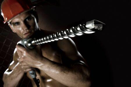 man close up: il lavoratore uomo bellezza driller vicino, maneggiare con perforatore