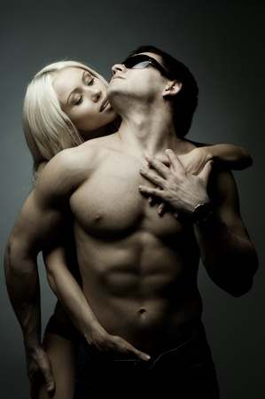 sexy young man: muscular handsome sexy guy with pretty woman, on dark background, glamour light Stock Photo