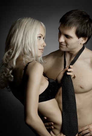 sexy couple embrace: muscular handsome sexy guy with pretty woman, on dark background, glamour  light