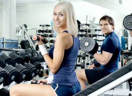 happy cutie athletic girl and guy,  exercise with dumbbells and smile, in  sport-hall