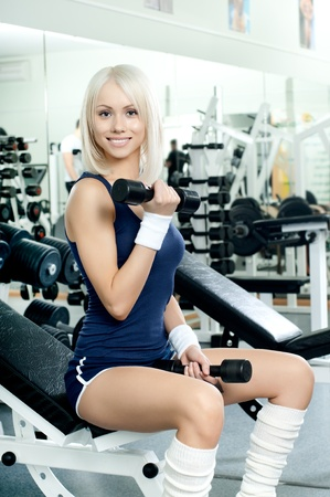 scrawny: happy cutie athletic girl ,  exercise with dumbbells and smile, in  sport-hall