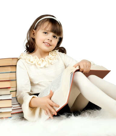 schoolgirls: the cute little girl lie with textbook and happy smile, on white background, isolated Stock Photo