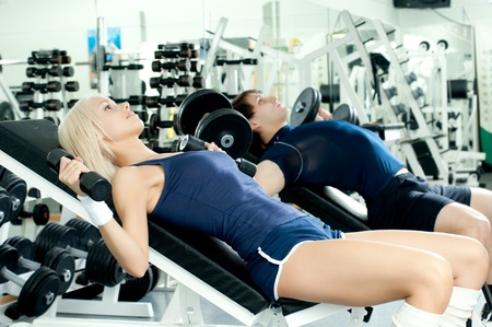 cutie athletic girl and guy,  execute exercise with dumbbells lie , in  sport-hall,  photo