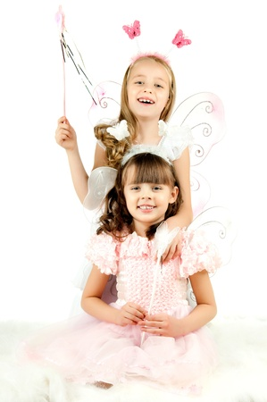 two beautiful  little girl with wings, sit and  fun game, smile,  on white background, isolated photo