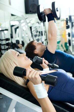 cutie athletic girl and guy,  execute exercise with dumbbells lie , in  sport-hall photo