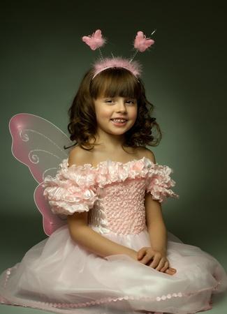 baby angel: bella bambina con le ali, sedersi e sorridere su sfondo scuro