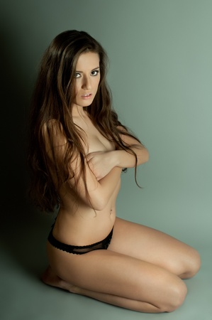 the very  pretty woman sit at the wall, light throug jalousie, hdark  long hair , sensual look photo