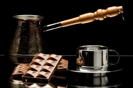 coffee pot: still life on mirror, coffee pot with polished surface steel  noggin and chocolate, on dark background