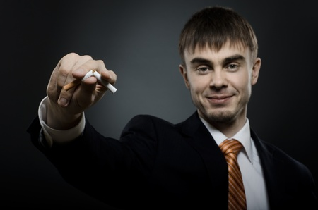 careerist: portrait  the  beautiful  businessman careerist in black costume give up smoking Stock Photo
