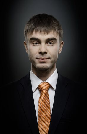 portrait  the  beautiful  businessman careerist in black costume and orange necktie Stock Photo - 12008744