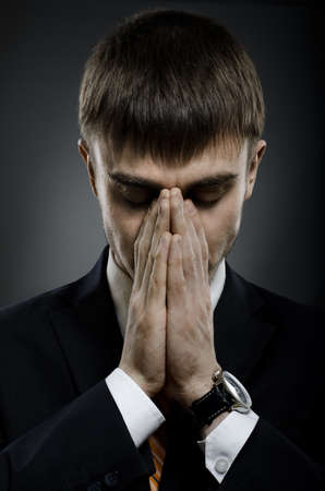careerist: portrait  the  businessman careerist in black costume grieve and praying
