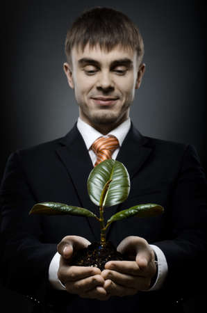 portrait  the  beautiful  businessman careerist in black costume with  scion  rubber plant photo