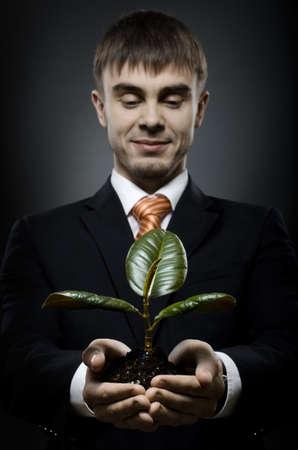 careerist: portrait  the  beautiful  businessman careerist in black costume with  scion  rubber plant
