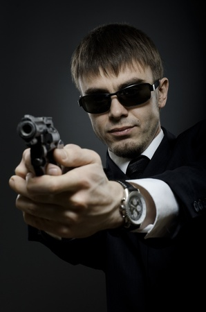 portrait  the  beautiful  man in black costume,  special-service agent or  body guard with  pistol Stock Photo - 12008747