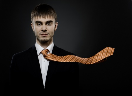 exacting: portrait  the  beautiful  businessman careerist in black costume and orange necktie Stock Photo