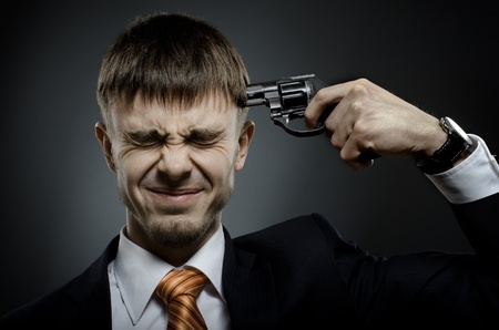 kill: closeup portrait  the  beautiful  businessman careerist in black costume to commit suicide Stock Photo