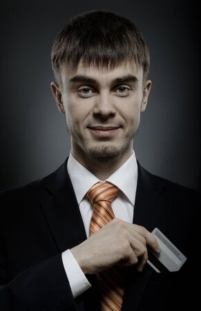 portrait  the  beautiful  businessman careerist in black costume and orange necktie with credit card Stock Photo - 12008751