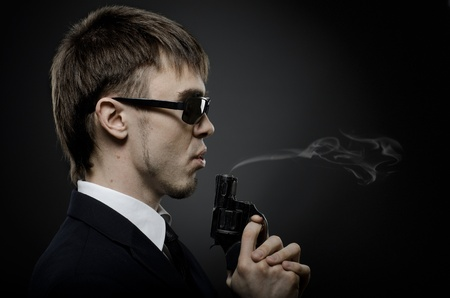 exacting: portrait  the  beautiful  man in black costume,  special-service agent or  body guard with  pistol Stock Photo
