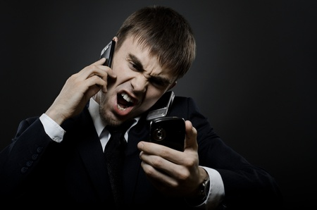 closeup portrait  the  beautiful  businessman careerist in black costume,  call and angry cry Stock Photo - 12008761
