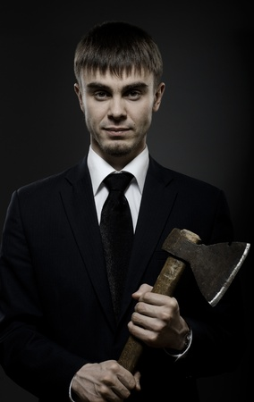 spiteful: portrait  the  beautiful  businessman careerist in black costume and black necktie with axe Stock Photo