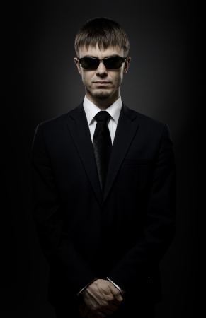body guard: portrait  the  beautiful  man in black costume,  special-service agent or  body guard