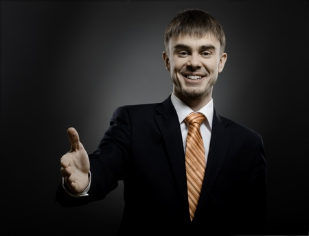 portrait  the  beautiful  businessman in black costume and orange necktie reach out  hand for handshake Stock Photo - 12008767