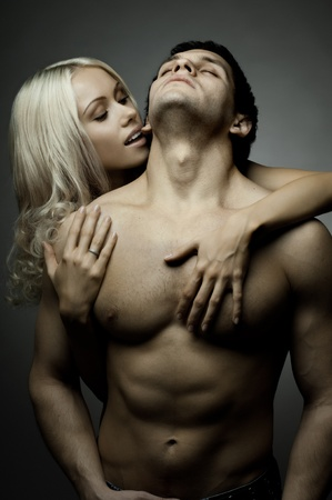 muscularity: muscular handsome sexy guy with pretty woman, on dark background, glamour light Stock Photo