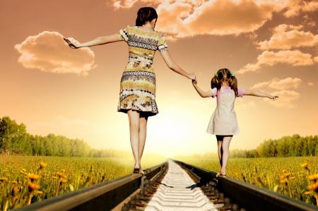 balanza: Madre con la hija van sobre ra�les, una vuelta a la c�mara, en el campo, en el verano Foto de archivo