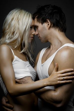 passionate embrace: muscular handsome sexy guy with pretty woman, on dark background, glamour light Stock Photo