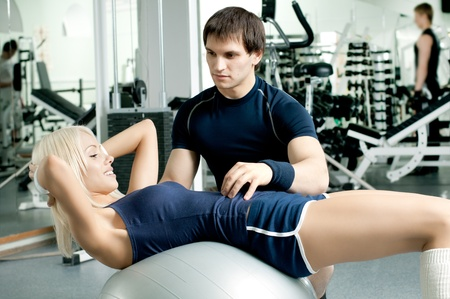 happy cutie athletic girl and guy,  execute exercise on sport-apparatus  and smile, in  sport-hall photo