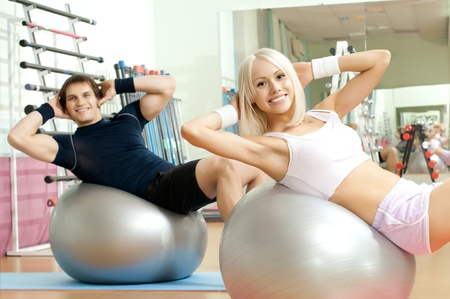 cutie: happy cutie athletic girl and guy,  execute exercise on muscles belly  on balls and smile, in  sport-hall