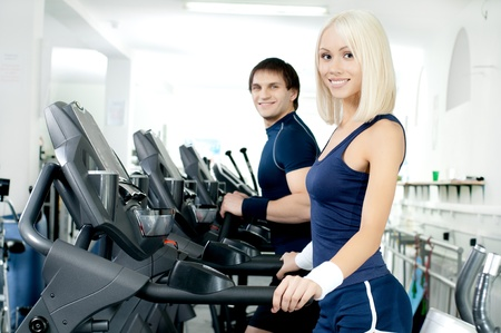 scrawny: happy cutie athletic girl and guy,  execute exercise on  running track  and smile, in  sport-hall Stock Photo