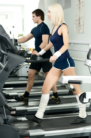 cutie: happy cutie athletic girl and guy,  execute exercise on  running track  and smile, in  sport-hall Stock Photo