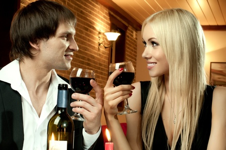 supper: romantic evening date in hotel room, or supper in restaurant, happy couple with wine glass
