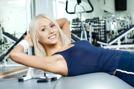 sporting event: happy cutie athletic girl ,  execute exercise on muscles belly  and smile, in  sport-hall