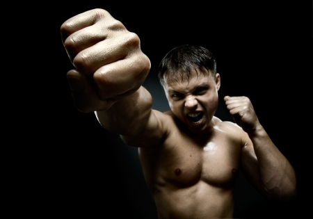 daring: horizontal photo  muscular young  guy street-fighter, cuff  fist close up on camera and yell , hard light