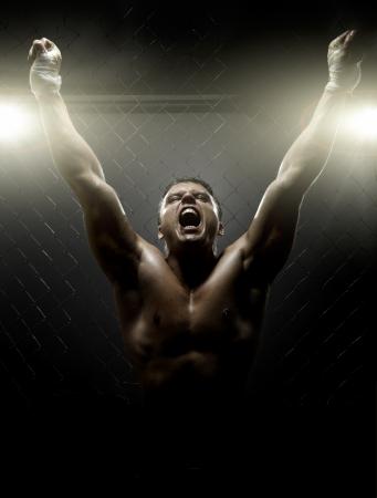 boxeadora: foto vertrical muscular joven luchador callejero, triunfante grito gritos, la luz dura Foto de archivo