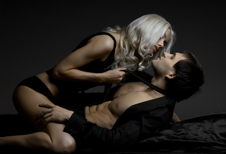female sex: muscular handsome sexy guy with pretty woman, on dark background, glamour  light