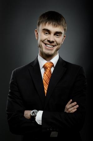 affability: portrait  the  beautiful  businessman careerist in black costume and orange necktie, big smile Stock Photo