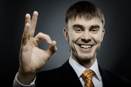 blithe: horizontal, el retrato del hombre de negocios hermosa en traje negro, para dar ok gesto de la mano
