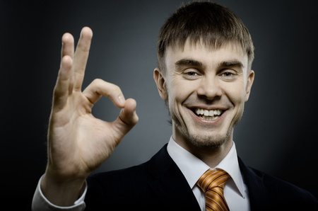 affability: horizontal portrait  the  beautiful  businessman in black costume , to give hand gesture ok Stock Photo