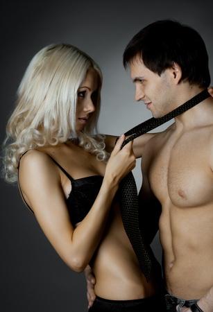 pareja apasionada: musculoso chico guapo sexy mujer hermosa, sobre fondo oscuro, la luz glamour