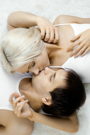 women kissing women: very happy  pretty couple, smile and kiss,  lie on white fur, close up Stock Photo