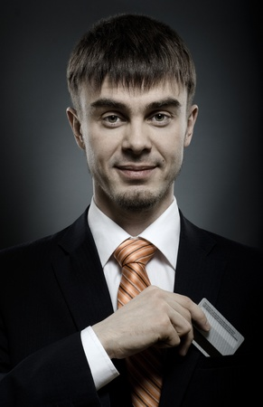 careerist: portrait  the  beautiful  businessman careerist in black costume and orange necktie with credit card