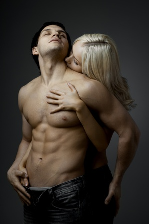 muscular handsome sexy guy with pretty woman, on dark background, glamour light Stock Photo