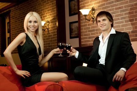 romantic evening date in hotel room,  happy couple with wine glass sit on red sofa photo