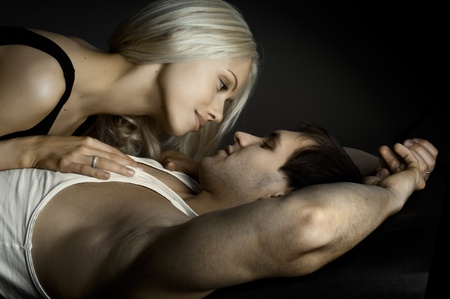 passionate: muscular handsome sexy guy with pretty woman, on dark background, glamour  light