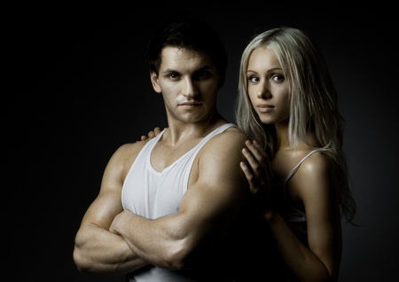 svelte: muscular handsome sexy guy with pretty woman on dark background, look on camera Stock Photo